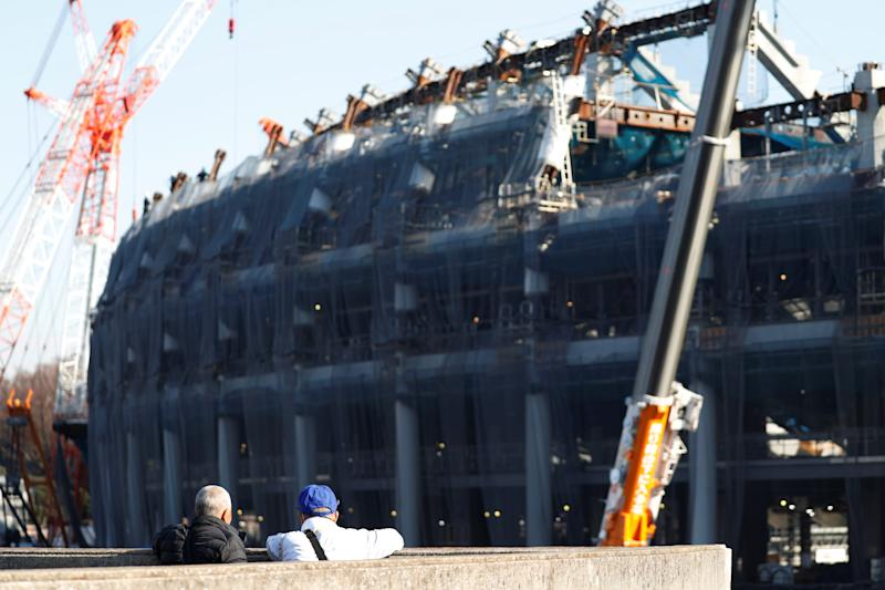 Men looks at the construction site of the New National Stadium main stadium of Tokyo 2020 More