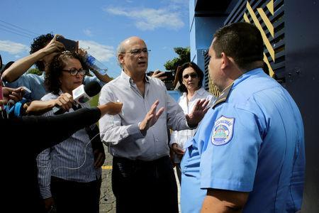 Journalist Carlos Fernando Chamorro, critic of the government of President Daniel Ortega speaks with a police officer during his arrival at police headquarters in Managua, Nicaragua December 15, 2018. REUTERS/Oswaldo Rivas