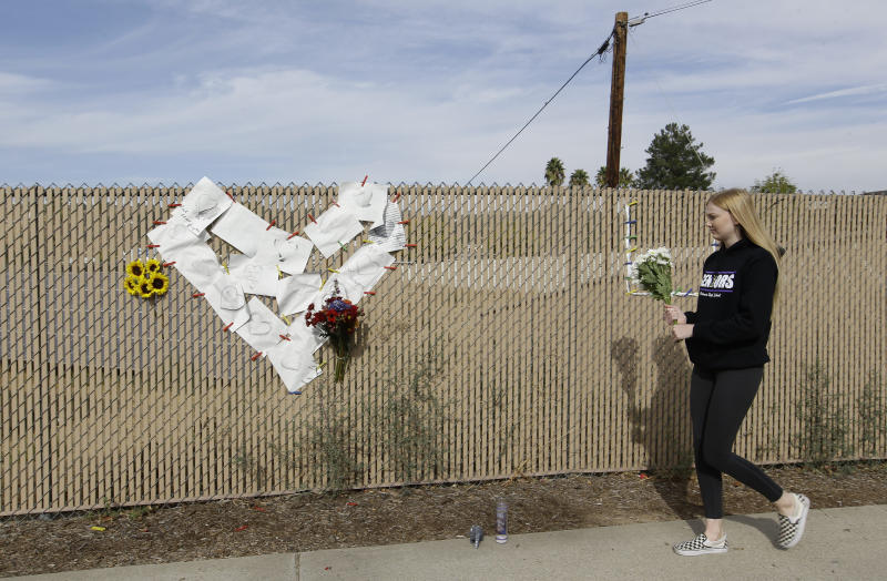 Emily Boyle, a senior at Valencia High School brings flowers at a memorial near Saugus High School in Santa Clarita, Calif., Friday, Nov. 15, 2019. A homicide official says that investigators did not find a diary, manifesto or note belonging to the boy who killed two people outside his Southern California high school on his 16th birthday. Officials held a press conference Friday outside of the police station Santa Clarita. No motive or rationale has been established yet in the Thursday morning shooting at Saugus High School in the Los Angeles suburb of Santa Clarita. (AP Photo/Damian Dovarganes)