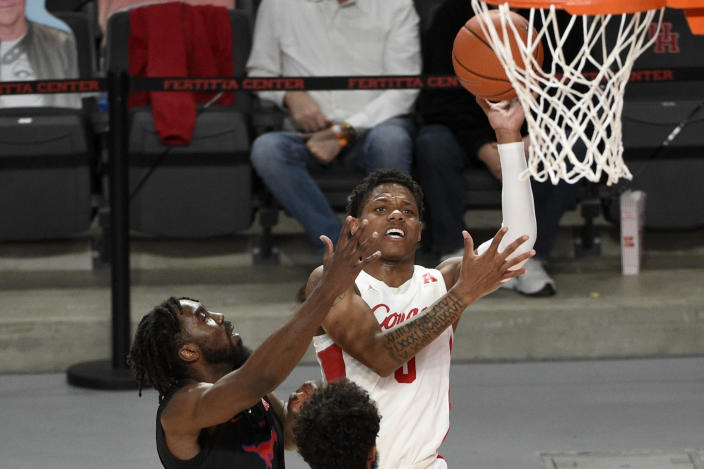 Houston guard Marcus Sasser, right, shoots as SMU guard Emmanuel Bandoumel, left, defends during the first half of an NCAA college basketball game, Sunday, Jan. 31, 2021, in Houston. (AP Photo/Eric Christian Smith)