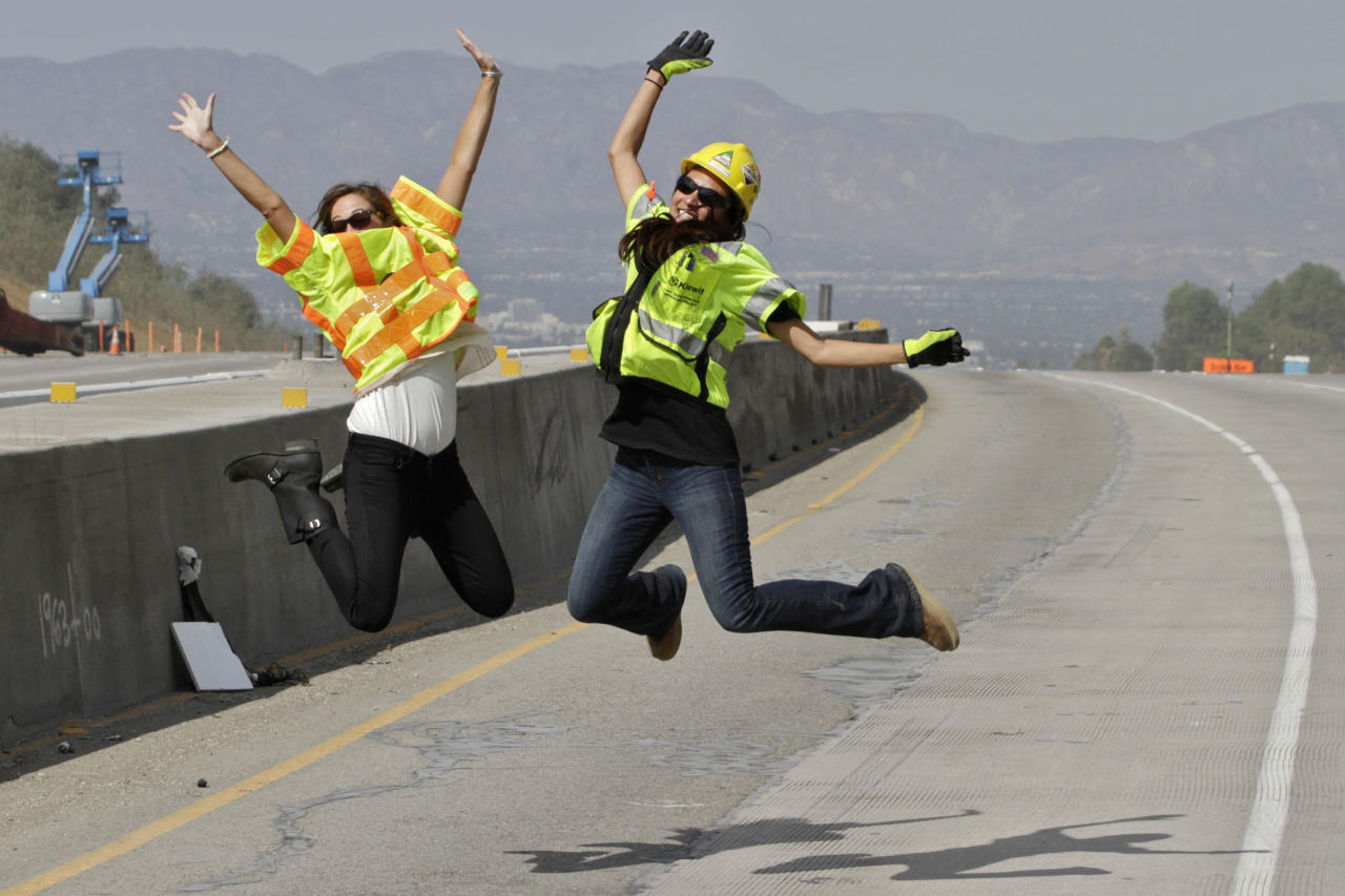 LOS ANGELES, CA -  SEPTEMBER 29:  Construction officials Kasey Shula (L) and Natasha Jones pose for a photo on the 405 Freeway as construction crews demolish a portion of the Mulholland Drive bridge along the 405 Freeway September 29, 2012 in Los Angeles, California. The 405 Freeway was completely shut down for a 10 mile stretch this weekend for the demolition that is part of a larger $1-billion freeway improvement project. (Photo by Jonathan Alcorn/Getty Images)