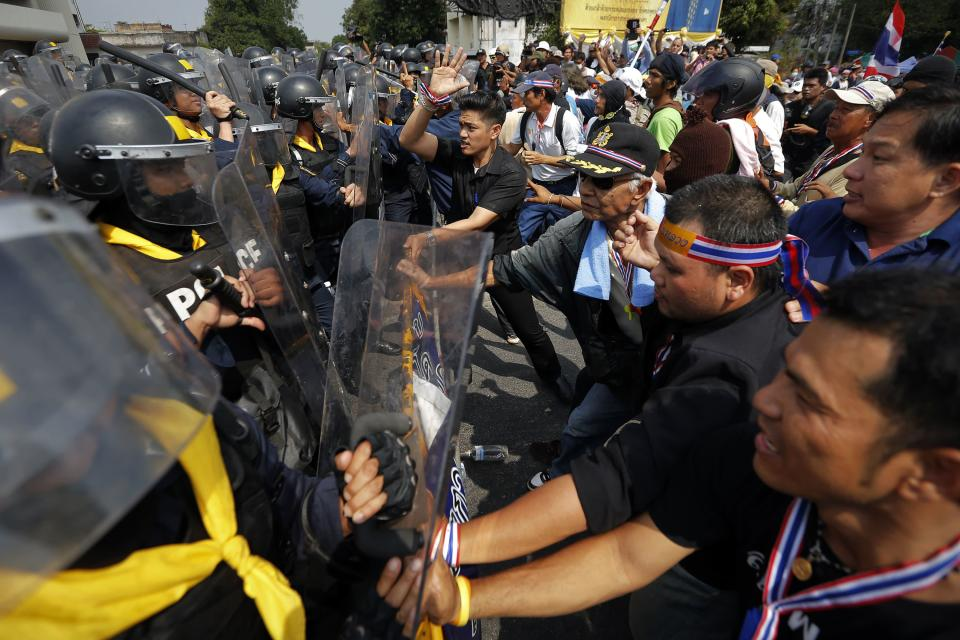 Policemen charge against anti-government protesters at one of their barricades near the Government House in Bangkok February 18, 2014. A Thai police officer was killed and dozens of police and anti-government protesters were wounded in gun battles and clashes in Bangkok on Tuesday, officials and witnesses said. REUTERS/Damir Sagolj (THAILAND - Tags: SOCIETY CIVIL UNREST POLITICS)