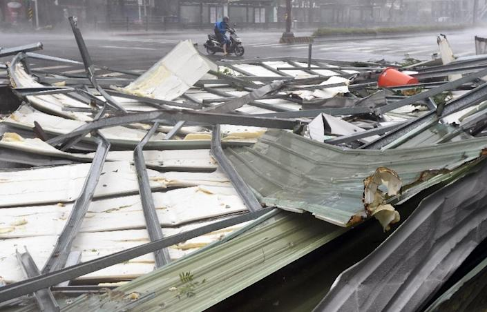 A motorcyclist rides past a damaged roof as Typhoon Soudelor hits Taipei on August 8, 2015 (AFP Photo/Sam Yeh)