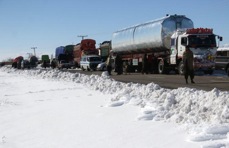 Vehicles are seen parked along the road, leading to the area with a heavy snowfall, on the outskirts of Quetta,