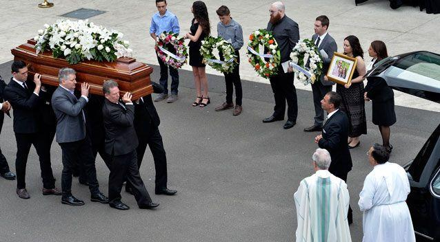 Loved ones were seen holding wreaths and photos as the caskets were walked out. Photo: AAP