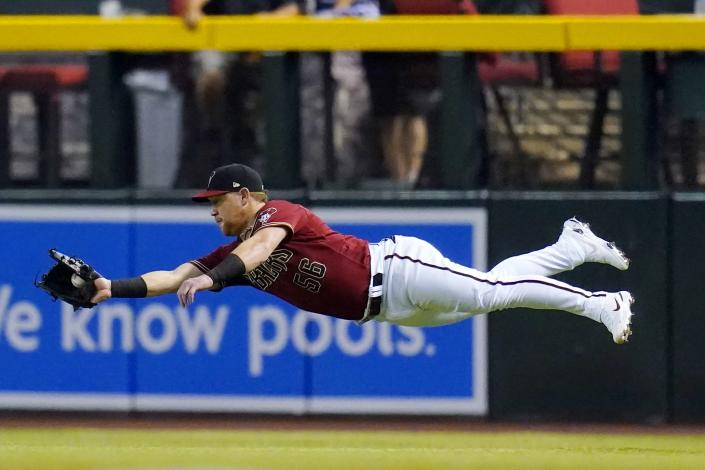Arizona Diamondbacks right fielder Kole Calhoun makes a diving catch on a line drive hit by Chicago Cubs' Jake Marisnick during the second inning of a baseball game, Sunday, July 18, 2021, in Phoenix. (AP Photo/Ross D. Franklin)