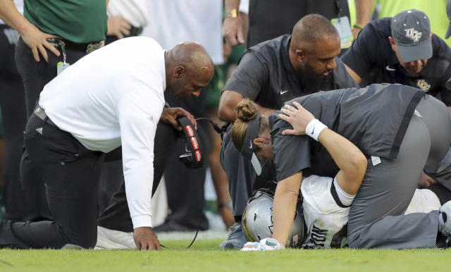 "South Florida coach Charlie Strong comforts Central Florida quarterback <a class=""link rapid-noclick-resp"" href=""/ncaaf/players/270182/"" data-ylk=""slk:McKenzie Milton"">McKenzie Milton</a>, after injuring his right leg on Nov. 23, 2018, in Tampa, Fla. (AP Photo/Mike Carlson)"