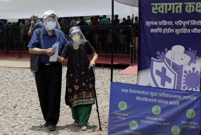 People wearing face shields and masks as a precaution against the coronavirus arrive to receive COVID-19 vaccine in Mumbai, India, Thursday, April 29, 2021. India set another global record in new virus cases Thursday, as millions of people in one state cast votes despite rising infections and the country geared up to open its vaccination rollout to all adults amid snags. (AP Photo/Rajanish Kakade)