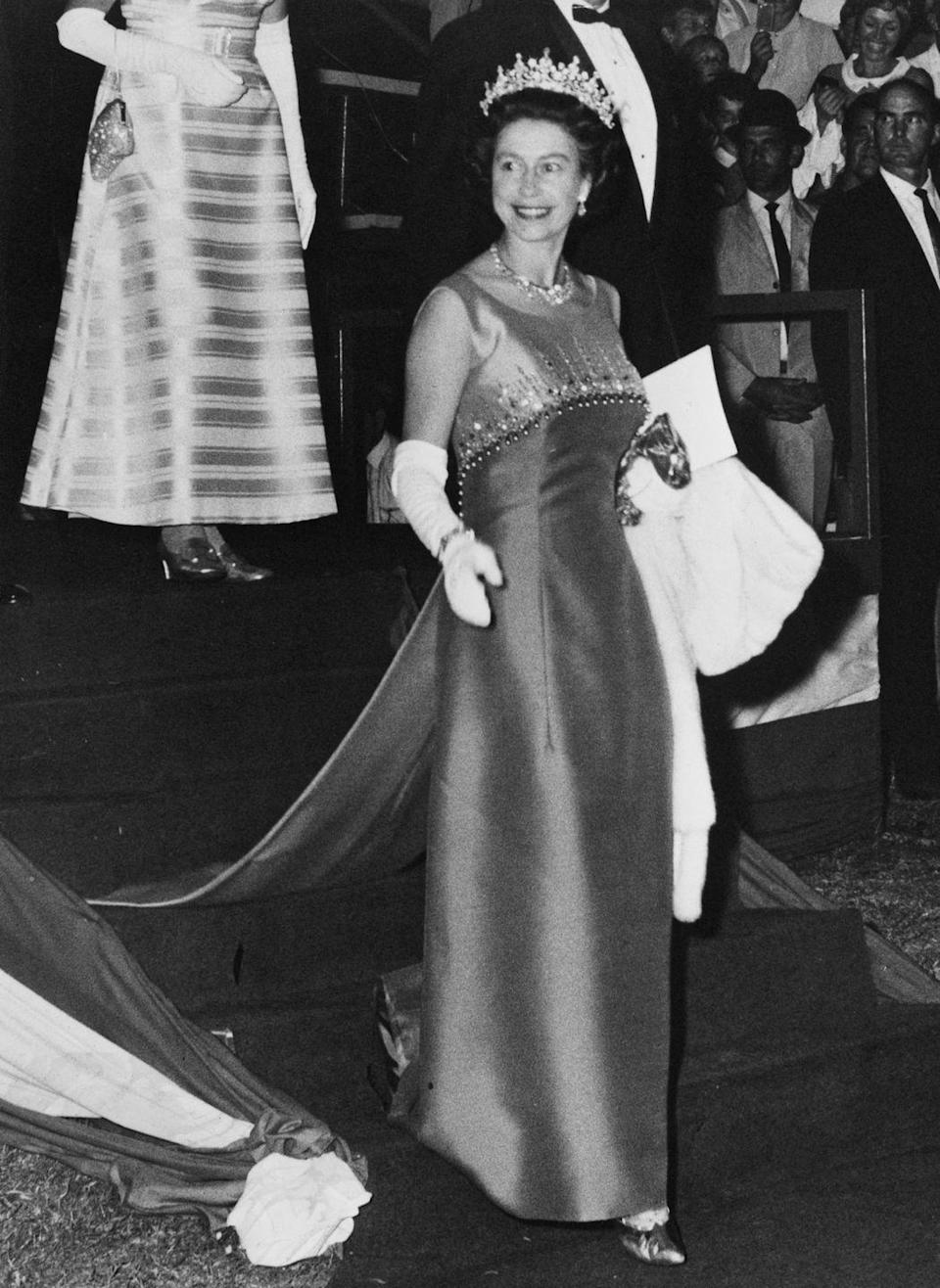 <p>Queen Elizabeth stunned during her royal tour of Australia in a sleeveless satin sheath evening gown. The regal dress was completed with a crystal embellished bodice and train. </p>