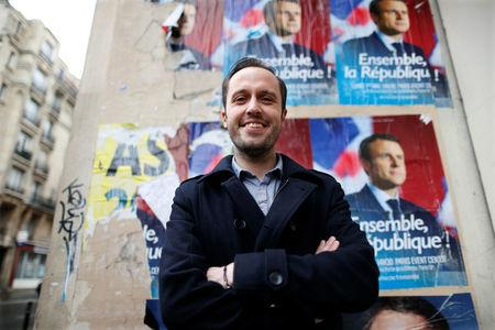 Christophe Brunelle, a teacher and campaigner for Emmanuel Macron, candidate for 2017 presidential election and head of the political movement En Marche !, or Onwards !, poses in front of campaign posters in Paris