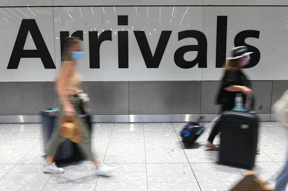 Passengers wearing face masks as a precautionary measure against COVID-19, walk through the arrivals hall after landing at London Heathrow Airport in west London, on January 15, 2021. - International travellers will need to present proof of a negative coronavirus test result in order to be allowed into England, or face a £500 ($685, 564 euros) fine on arrival, from January 18. (Photo by DANIEL LEAL-OLIVAS / AFP) (Photo by DANIEL LEAL-OLIVAS/AFP via Getty Images)
