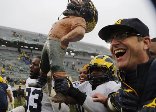 Michigan tight end Zach Gentry (83), linebacker Devin Bush, and head coach Jim Harbaugh walk off the field with the Paul Bunyan trophy after an NCAA college football game against Michigan State, Saturday, Oct. 20, 2018, in East Lansing, Mich. Michigan won 21-7. (AP Photo/Carlos Osorio)