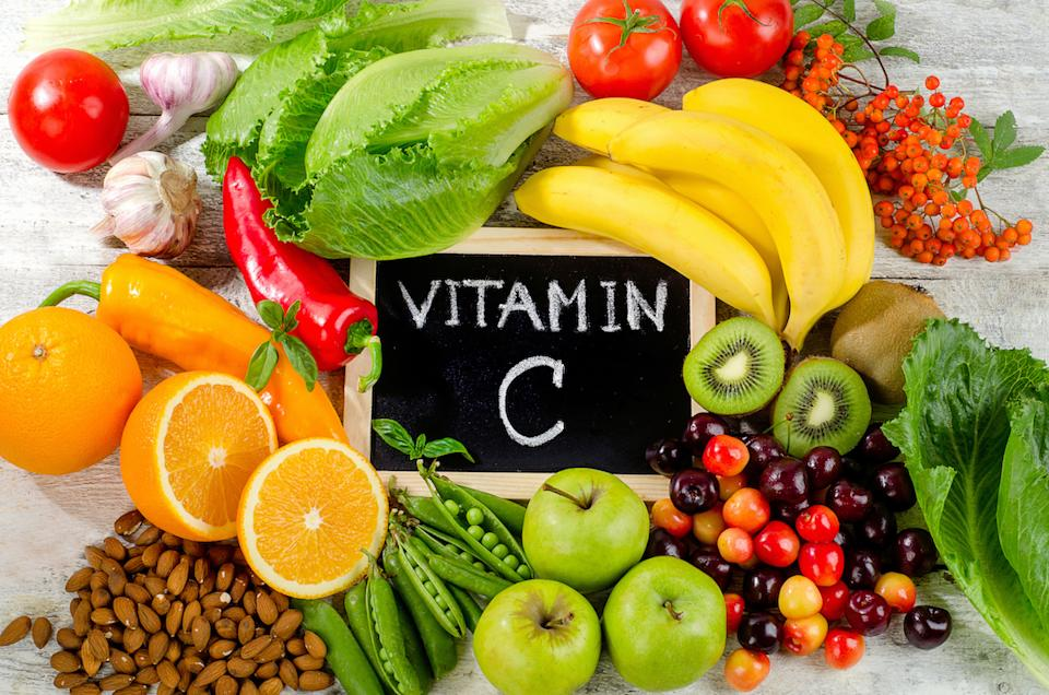 Foods High in vitamin C on a wooden board, including oranges, almonds, kiwis, bananas, peppers, and more