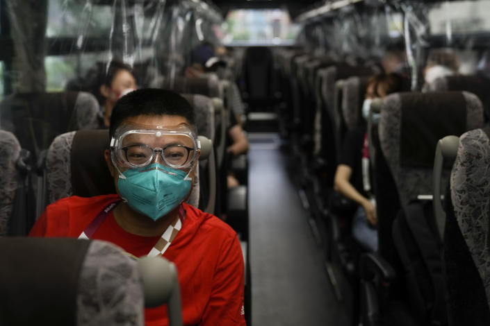Hua Zhang, of the China Media Group, wears protective goggles while riding a media bus ahead the 2020 Summer Olympics, Wednesday, July 14, 2021, in Tokyo. (AP Photo/Jae C. Hong)
