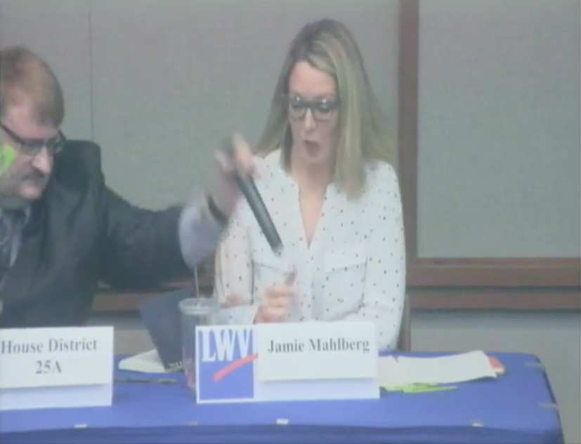 Rep. Duane Quam, R-Minn., grabs the microphone out of opponent Jamie Wahlberg's hand during a debate. (Photo: rochestercitymn)