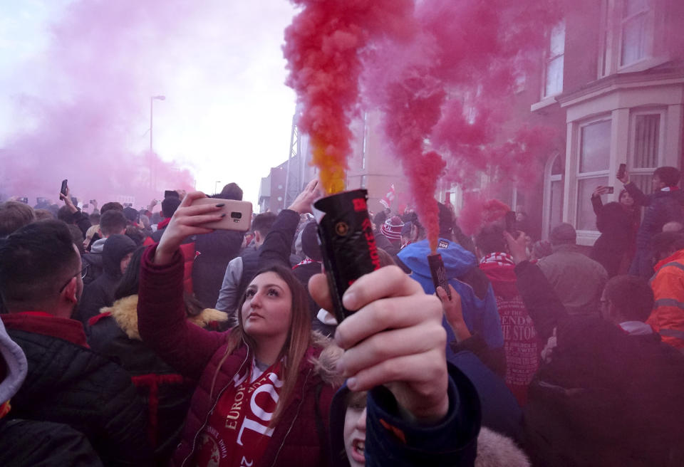 Football supporters set off flares before the English Premier League soccer match between Liverpool and Manchester United near Anfield Stadium in Liverpool, Sunday, Jan. 19, 2020.(AP Photo/Jon Super)