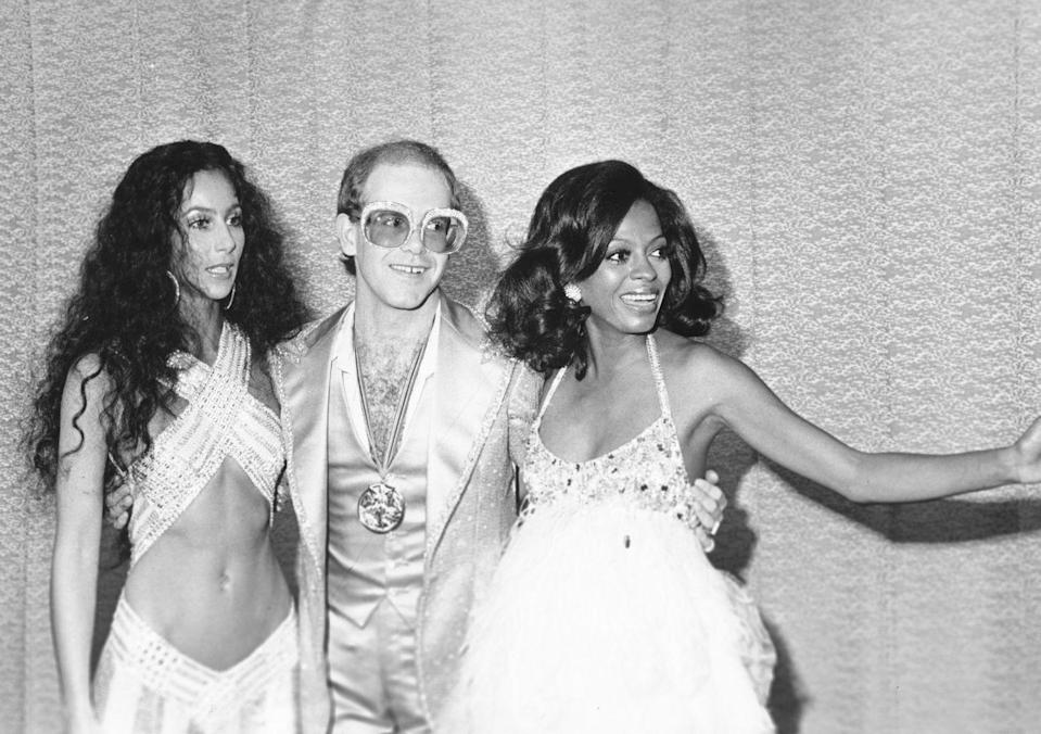 <p>Cher, Elton John, and Diana Ross pose together while backstage at the first Rock Music Awards in Los Angeles in 1975. </p>