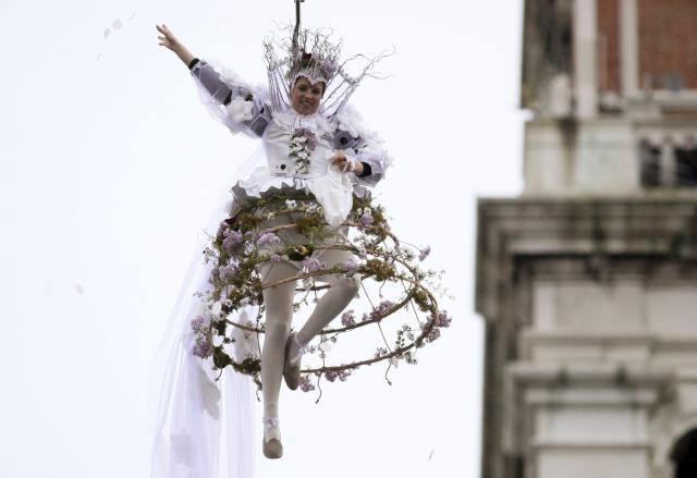 Figure skating bronze medallist at the recent Sochi Winter Olympics Italy's Carolina Kostner performs as the traditional Columbine, as she descends from Saint Mark's bell tower on an iron cable, during the Venetian Carnival in Venice, March 2, 2014. REUTERS/Manuel Silvestri (ITALY - Tags: SOCIETY SPORT FIGURE SKATING OLYMPICS)