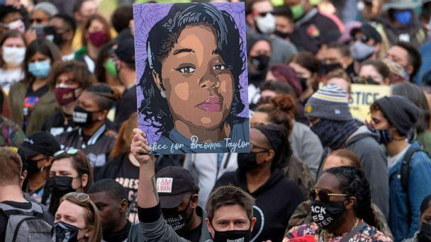 PHOTO: A protestor brandishes a portrait of Breonna Taylor during a rally in remembrance on the one year anniversary of her death in Louisville, Kentucky, March 13, 2021.  (Jeff Dean/AFP via Getty Images)