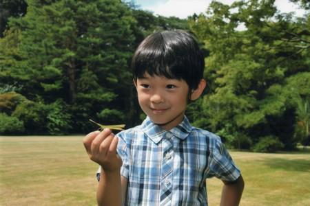 FILE PHOTO: Japan's Prince Hisahito holds a grasshopper in the Akasaka imperial estate in Tokyo in this handout photo by the Imperial Household Agency of Japan