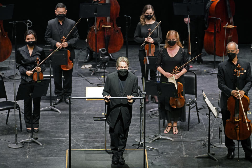 Guest conductor Esa Pekka Salonen, front center, greets a live audience as New York Philharmonic musicians stand behind him before they performed together for the first time since March 10, 2020, at The Shed in Hudson Yards, Wednesday, April 14, 2021, in New York. Normal subscription performances are scheduled to resume in September. (AP Photo/Kathy Willens)