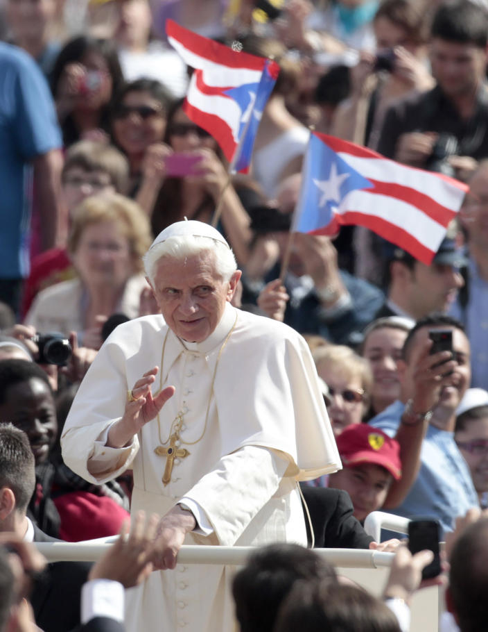Pope Benedict XVI blesses the faithful as he tours St. Peter's square aboard the Pope mobile at the Vatican, Wednesday, April 4, 2012. (AP Photo/Gregorio Borgia)