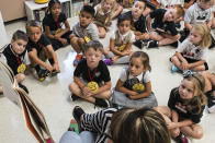 FILE — In this Aug. 22, 2018, file photo, students from two kindergarten classes at the Lewiston elementary campus of Saint Dominic Academy, listen to a teacher read a book, in Lewiston, Maine. School districts across the United States are hiring additional teachers in anticipation of what will be one of the largest kindergarten classes ever as enrollment rebounds following the pandemic. (Russ Dillingham/Sun Journal via AP, File)