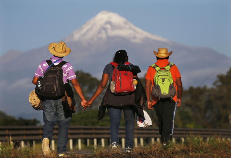 In this Nov. 5, 2018 photo, Central American migrants begin their morning trek facing Pico de Orizaba volcano as part of a thousands-strong caravan hoping to reach the U.S. border, upon departure from Cordoba, Veracruz state, Mexico. A big group of Central Americans pushed on toward Mexico City from a coastal state Monday, planning to exit a part of the country that has long been treacherous for migrants seeking to get to the United States. (AP Photo/Marco Ugarte)