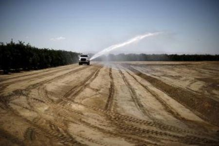 Trucks work on constructing a reservoir on Gless Ranch in Kern County