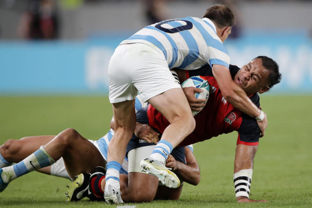 England's Billy Vunipola carries the ball against Argentina defense during the Rugby World Cup Pool C game at Tokyo Stadium in Tokyo, Japan, Saturday, Oct. 5, 2019. (AP Photo/Christophe Ena)