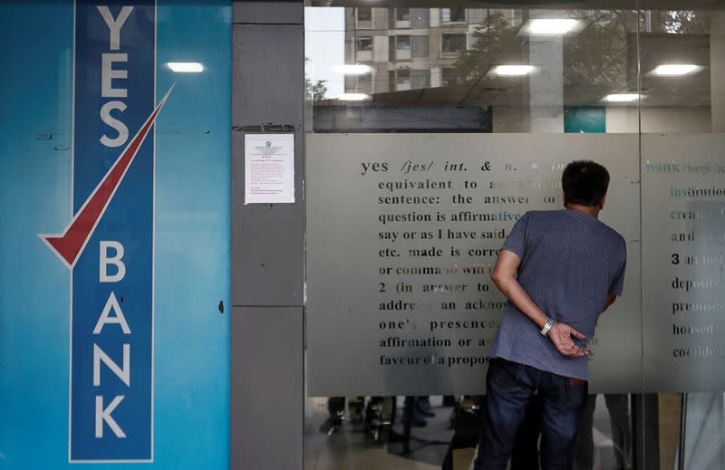 A customer tries to look into a Yes Bank branch in Mumbai
