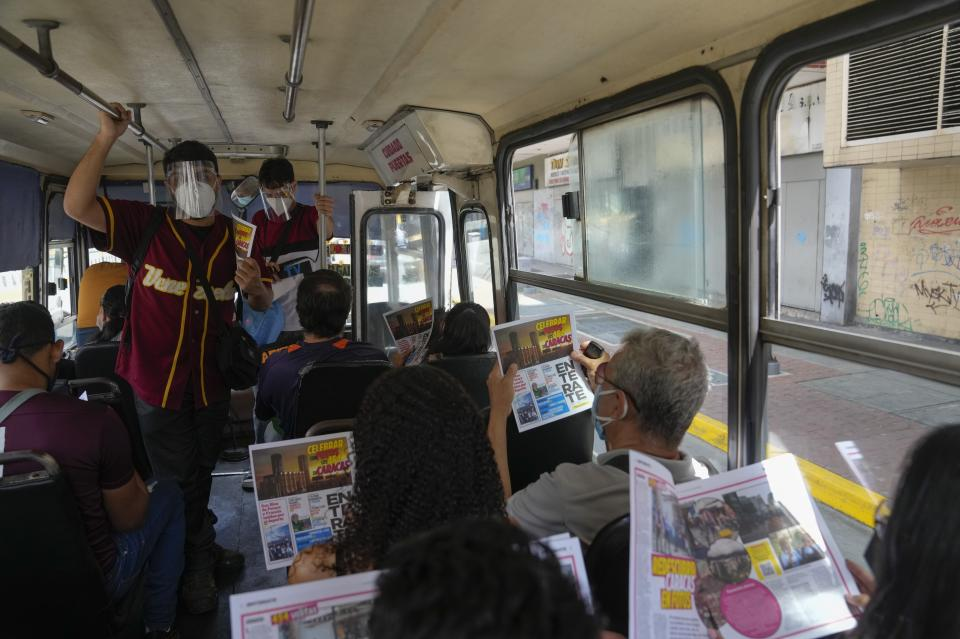 """Juan Pablo Lares, left, talks to bus passengers as he and his associate Maximiliano Bruzual deliver their newscast """"El Bus TV Capitolio"""" and hand out free copies of the newspaper """"Enterate,"""" in Caracas, Venezuela, Saturday, July 31, 2021. Two decades of governments that see the press as an enemy have pushed Venezuelan journalists to find alternative ways to keep citizens informed. (AP Photo/Ariana Cubillos)"""