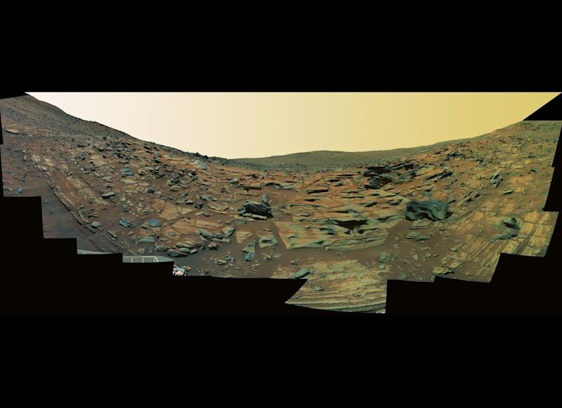 "This Spirit Pancam false-color panorama from mission sols 748-751 (February 9-12, 2006) shows what could be finely-layered lithified ash fall deposits along the edge of an ancient, worn-down volcanic cinder cone called Home Plate. <em>From ""Postcards from Mars"" by Jim Bell; Photo credit: NASA/JPL/Cornell University</em>"