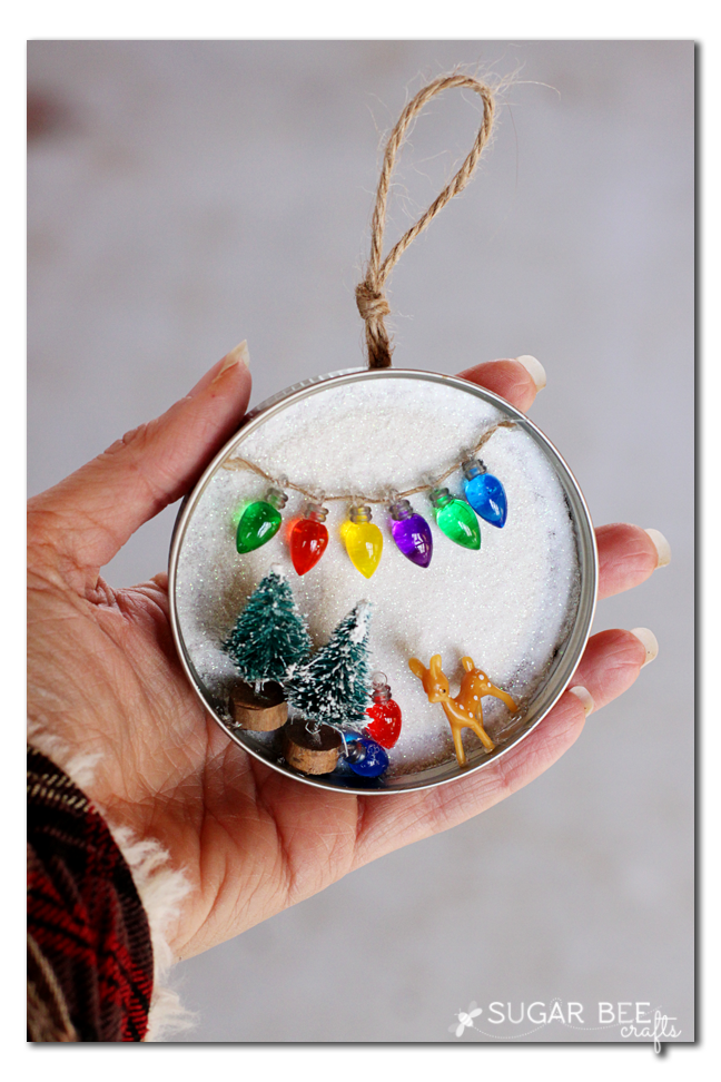 """<p>Re-create the concept of a snow globe without worrying about it breaking. This tiny scene was made using the lid of a Mason jar.</p><p><strong>Get the tutorial at <a href=""""https://sugarbeecrafts.com/mason-jar-lid-snowy-scene-decor-ornament"""" rel=""""nofollow noopener"""" target=""""_blank"""" data-ylk=""""slk:Sugar Bee Crafts"""" class=""""link rapid-noclick-resp"""">Sugar Bee Crafts</a>.</strong></p><p><strong><a class=""""link rapid-noclick-resp"""" href=""""https://www.amazon.com/Hemway-Craft-Glitter-3-5oz-Ultrafine/dp/B07KRCFJQ3/?tag=syn-yahoo-20&ascsubtag=%5Bartid%7C10050.g.2132%5Bsrc%7Cyahoo-us"""" rel=""""nofollow noopener"""" target=""""_blank"""" data-ylk=""""slk:SHOP WHITE GLITTER"""">SHOP WHITE GLITTER</a><br></strong></p>"""