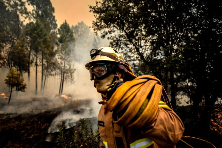 A firefighter carries a hose as a fire squad tries to extinguish a wildfire in the village of Casais de Sao Bento in Macao in central Portugal on July 22, 2019. (Photo: Patricia De Melo Moreira/AFP/Getty Images)