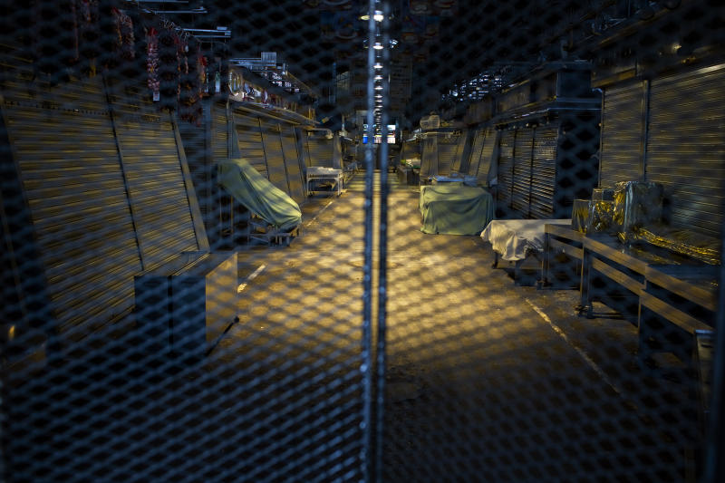 A view of La Boqueria market closed down in downtown Barcelona, Spain, Thursday, March 26, 2020. The new coronavirus causes mild or moderate symptoms for most people, but for some, especially older adults and people with existing health problems, it can cause more severe illness or death. (AP Photo/Emilio Morenatti)