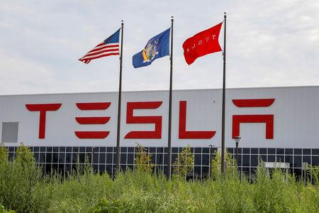 FILE PHOTO: Flags fly over the Tesla Inc. Gigafactory 2, also known as RiverBend, a joint venture with Panasonic to produce solar panels and roof tiles in Buffalo, New York, U.S., August 2, 2018.  REUTERS/Brendan McDermid/File Photo