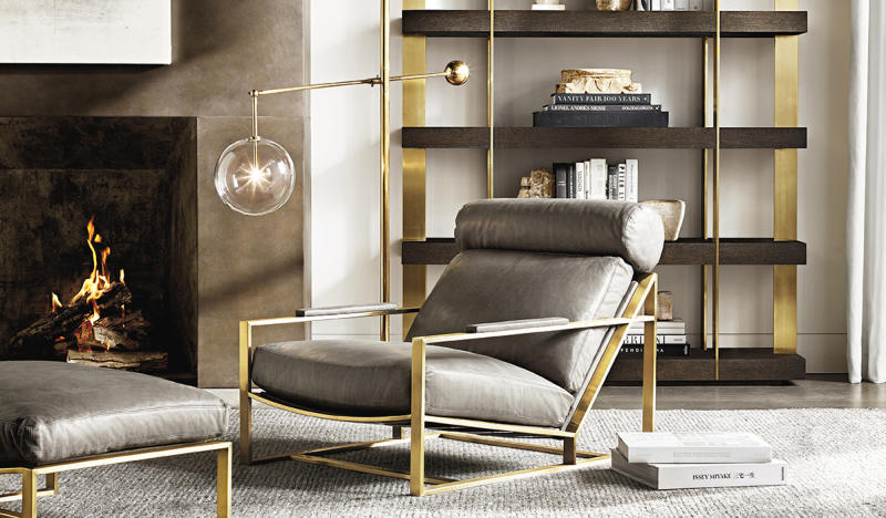 Living room set in gray and gold with chair, ottoman, shelves, and lamp.