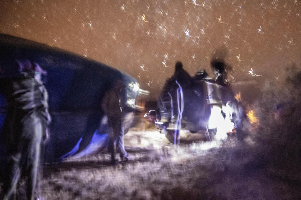 Smugglers gather near and pause atop a vehicle as they attempt to lift a fishing boat in a remote desert out of the town of Dakhla in Morocco-administered Western Sahara, Tuesday, Dec. 22, 2020. (AP Photo/Mosa'ab Elshamy)