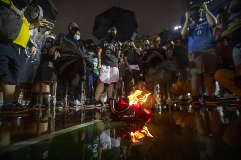 Demonstrators watch as a Lebron James jersey burns during a rally at the Southorn Playground in Hong Kong, Tuesday, Oct. 15, 2019. Protesters in Hong Kong have thrown basketballs at a photo of LeBron James and chanted their anger about comments the Los Angeles Lakers star made about free speech during a rally in support of the NBA and Houston Rockets general manager Daryl Morey, whose tweet in support of the Hong Kong protests touched off a firestorm of controversy in China. (AP Photo/Mark Schiefelbein)