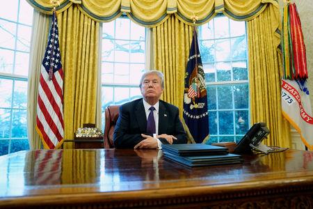 U.S. President Donald Trump sits at his desk after signing directives to impose tariffs on imported washing machines and solar panels in the Oval Office at the White House in Washington, U.S., January 23, 2018.  REUTERS/Jonathan Ernst