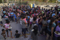 """FILE - In this Aug. 30, 2019, file photo, migrants, most of who are asylum seekers that have been sent back to Mexico under the Migrant Protection Protocols, to wait for their asylum cases, stand in line to get a meal in an encampment near the Gateway International Bridge in Matamoros, Mexico. The Supreme Court has ordered the reinstatement of the """"Remain in Mexico"""" policy, saying that the Biden administration likely violated federal law by trying to end the Trump-era program that forces people to wait in Mexico while seeking asylum in the U.S. (AP Photo/Veronica G. Cardenas, File)"""