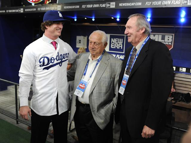 Pitcher Grant Holmes, left, from Conway High School in South Carolina talks with Hall of Famers Tommy Lasorda and Charlie Hough, right, at the 2014 MLB baseball draft Thursday, June 5, 2014, in Secaucus, N.J. Holmes was selected by the Los Angeles Dodgers with the 22nd pick in the first round. (AP Photo/Bill Kostroun)