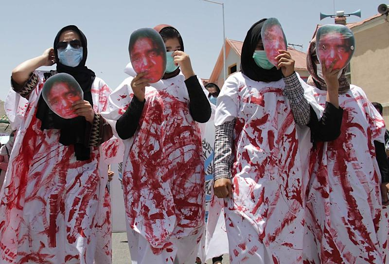 Afghan women wear masks of 27 year-old Farkhunda who was beaten to death by a mob after being falsely accused of burning a Quran, during a protest held by the Solidarity Party of Afghanistan at the site of the attack in Kabul, Monday, July 6, 2015.