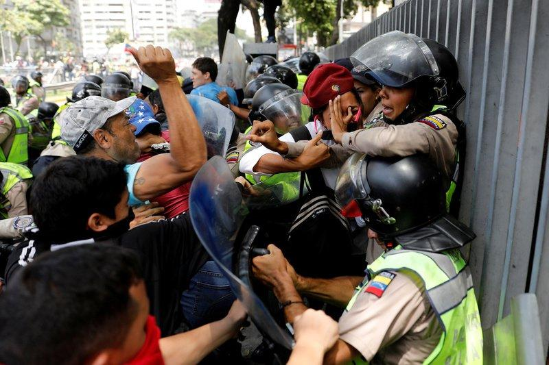 Demonstrators scuffle with security forces during an opposition rally in Caracas, Venezuela. REUTERS/Carlos Garcia Rawlins