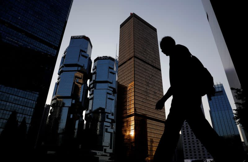 A man walks past buildings at a business district in Hong Kong