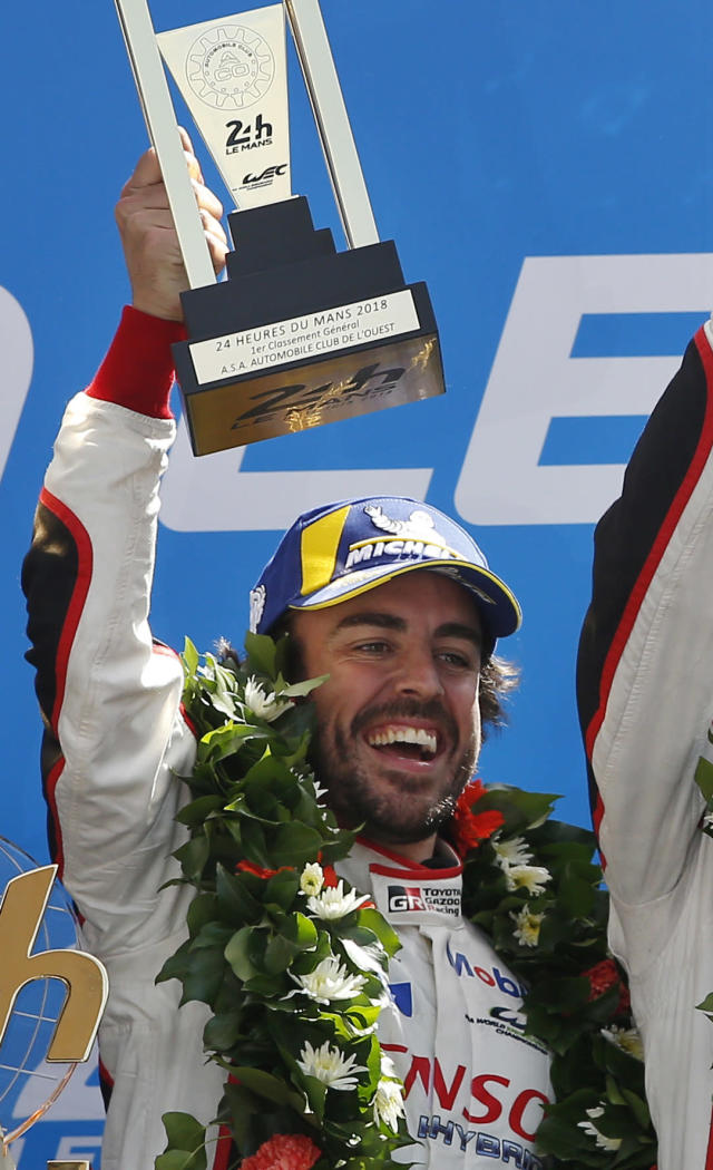 FILE - In this June 17, 2018, file photo, Fernando Alonso, of Spain, celebrates with teammates after winning the the 86th 24-hour Le Mans endurance race, in Le Mans, western France. McLaren will put a car on track at Indianapolis Motor Speedway for the first time since 1976 when Fernando Alonso tests Wednesday. Alonso is trying to win motorsports version of the Triple Crown, while the famed manufacturer is considering a return to IndyCar competition. (AP Photo/Thibault Camus, File)