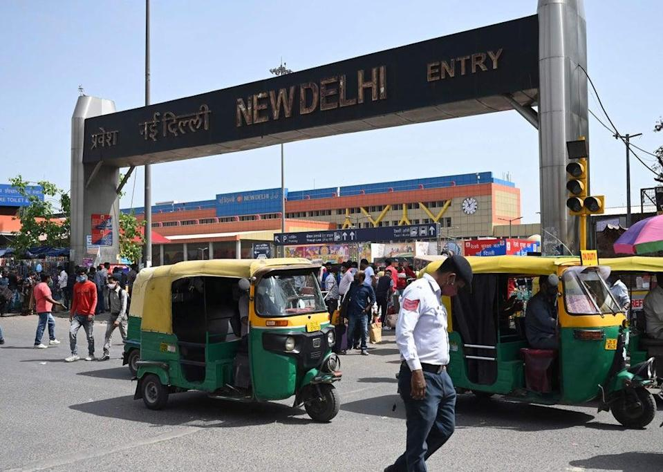 A traffic policeman, people and vehicles make their way near an entrance of the New Delhi Railway (AFP via Getty Images)