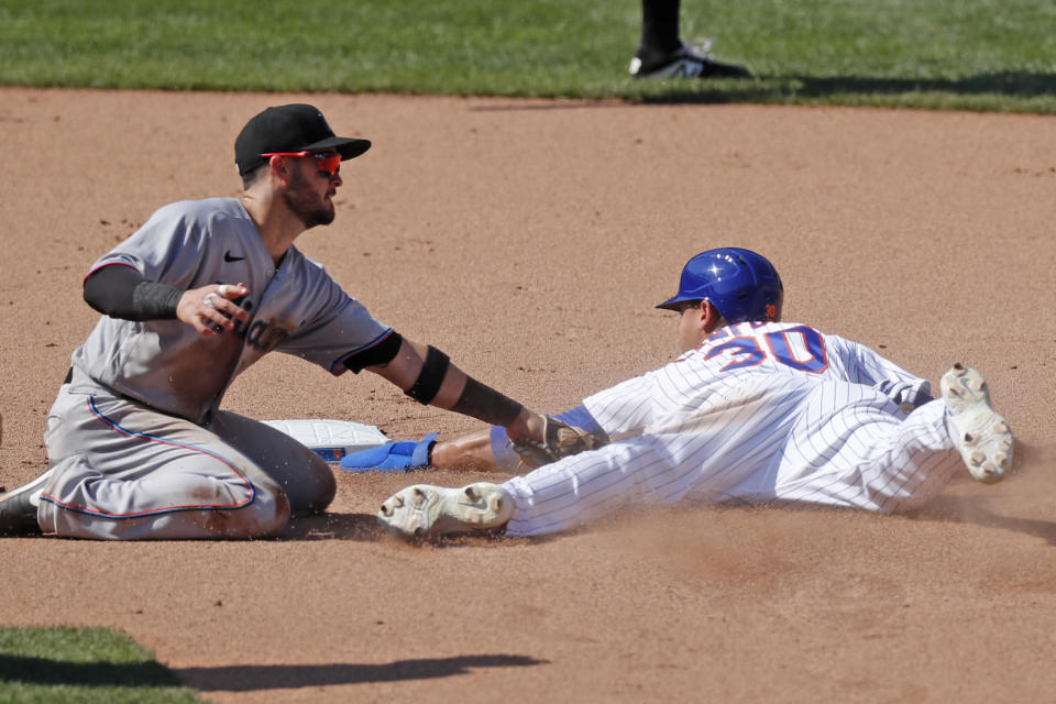 Miami Marlins second baseman Eddy Alvarez, left, tags out New York Mets' Michael Conforto (30) stealing second during the seventh inning of a baseball game at Citi Field, Sunday, Aug. 9, 2020, in New York. The Marlins challenged the call on the field and it was overturned in the challenge. (AP Photo/Kathy Willens)