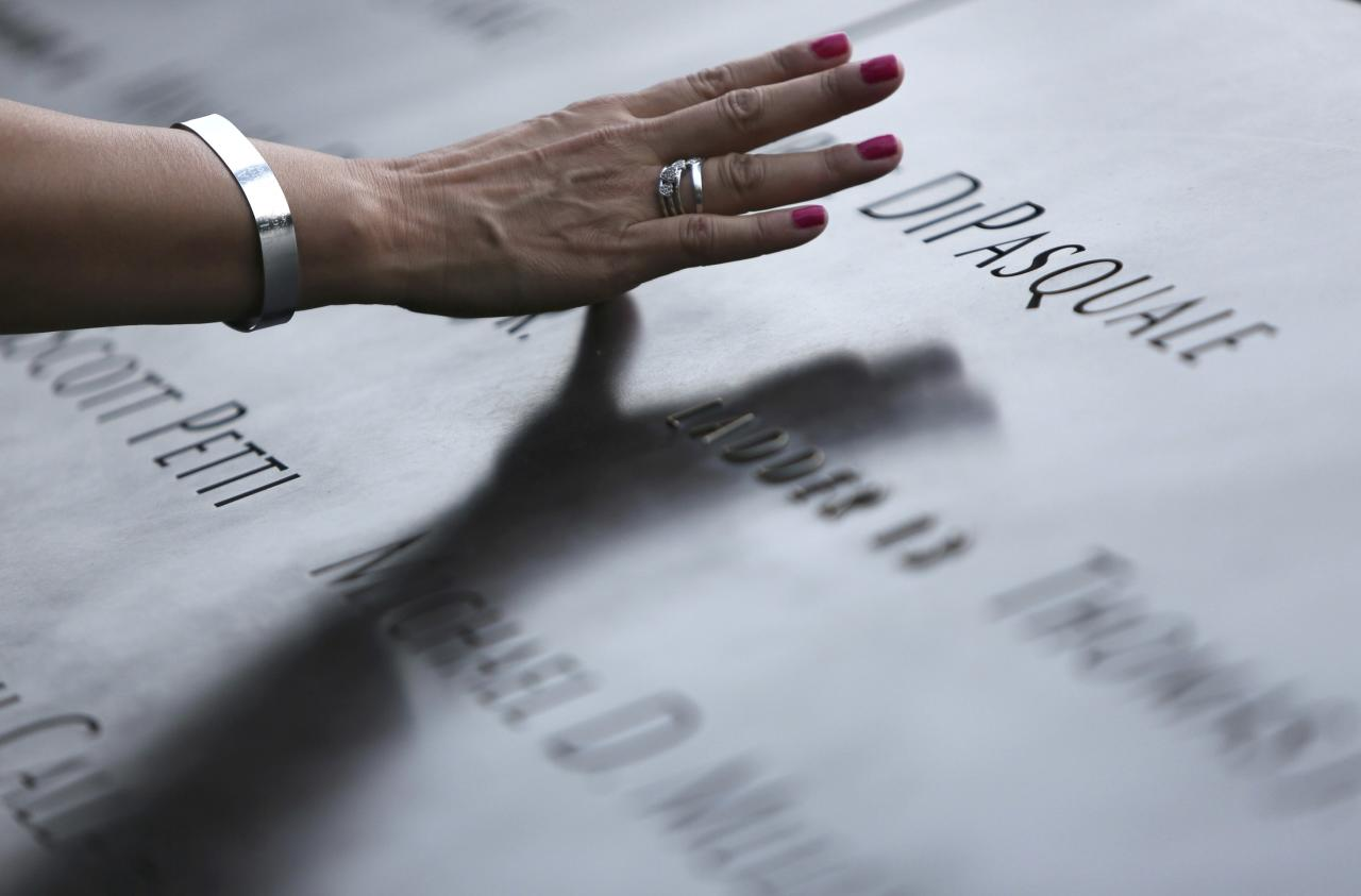 An attendee touches the stone with names of victims at the 9/11 Memorial during ceremonies marking the 12th anniversary of the 9/11 attacks on the World Trade Center in New York September 11, 2013. REUTERS/Chris Pedota/Pool (UNITED STATES - Tags: DISASTER ANNIVERSARY TPX IMAGES OF THE DAY)